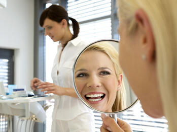 Dental-patient-smiling-in-mirror-1